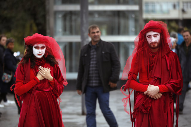 Extinction Rebellion climate change protesters call for action on climate change by staging an event against the fashion industry outside a shopping centre in Istanbul, Friday, November 29, 2019. (Photo by Lefteris Pitarakis/AP Photo)