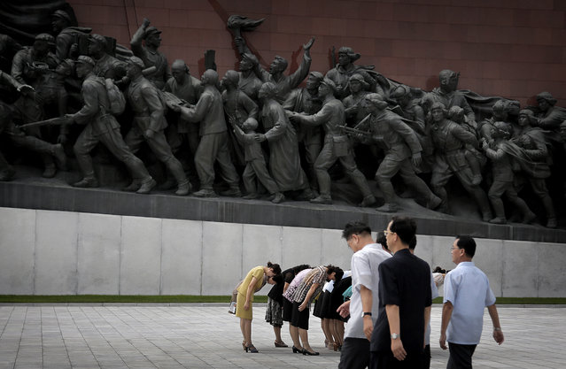 North Koreans bow to bronze statues of the late leaders Kim Il Sung and Kim Jong Il at Munsu Hill, Monday, July 27, 2015, in Pyongyang, North Korea. (Photo by Wong Maye-E/AP Photo)
