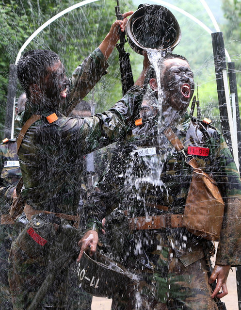 A South Korean army recruit pours water on his fellow recruit to cool off during their training at an Army training Center in Nonsan, South Korea, Friday, June 20, 2014. (Photo by Yang Yong-suck/AP Photo/Yonhap)