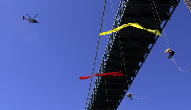 A Coast Guard helicopter flies overhead as activists unfurl colored banners while hanging from the St. Johns bridge in Portland, Ore., Wednesday, July 29, 2015, to protest the departure of Royal Dutch Shell PLC icebreaker Fennica, which is in Portland for repairs.  The icebreaker is a vital part of Shell's exploration and spill-response plan off Alaska's northwest coast. (Photo by Don Ryan/AP Photo)