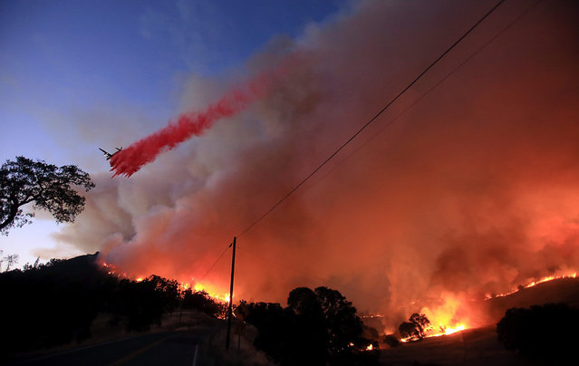 An air tanker drops retardant at the Rocky Fire as the wind picks up spreading the flames south down in the Morgan Valley during sunset, Wednesday July 29, 2015, near Lower Lake, Calif. (Photo by Kent Porter/The Press Democrat via AP Photo)