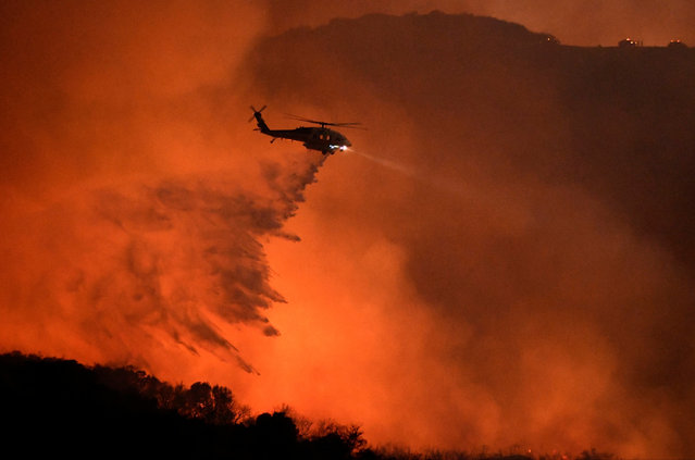 """A helicopter makes a water drop at the """"Old Fire"""", which burned in Calabasas, California, U.S., June 4, 2016. (Photo by Gene Blevins/Reuters)"""