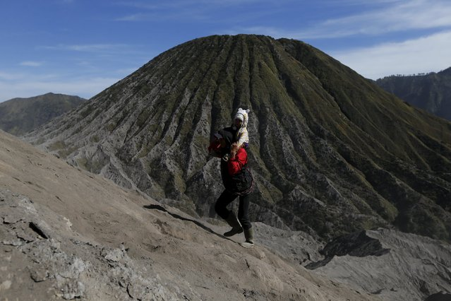 A man carries a child on his back as they climb the slope of Bromo mountain to attend the  Kasada Festival in Probolinggo, Indonesia's East Java province, August 1, 2015. (Photo by Reuters/Beawiharta)