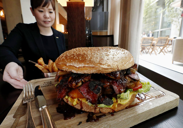 """In this Thursday, March 28, 2019, photo, a """"golden giant burger"""" is served at a restaurant of Hotel Grand Hyatt Tokyo in Tokyo. The $900 wagyu (Japanese-produced beef) burger was unveiled to commemorate the era change. What's in a name? Quite a lot if you're a Japanese citizen awaiting the official announcement Monday, April 1, 2019 of what the soon-to-be-installed new emperor's next era will be called. It's a proclamation that has happened only twice in nearly a century, and the new name will follow Emperor Naruhito, after his May 1 investiture, for the duration of his rule, attaching itself to much of what happens in Japan. (Photo by Kyodo News via AP Photo)"""