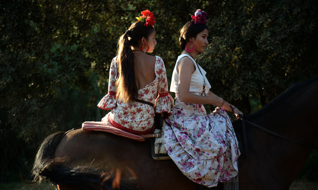 Pilgrims cross the Quema river on June 6, 2019 in Villamanrique, during a pilgrimage on their way to the village of El Rocio. El Rocio pilgrimage, the largest in Spain, gathers hundreds of thousands of devotees in traditional outfits converging in a burst of colour as they make their way on horseback and on board decorated carriages across the Andalusian countryside. (Photo by Cristina Quicler/AFP Photo)