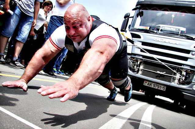 An athlete pulls a 15-tonne truck during a Truck-Pull event marking the upcoming Independence Day in the Belarus capital Minsk, on July 3, 2014. The former Soviet nation celebrates its Independence Day on July 3 in memory of the end of Belarus occupation by Nazi Germany troops during the Red Army main summer offensive in 1944. (Photo by Sergei Gapon/AFP Photo)