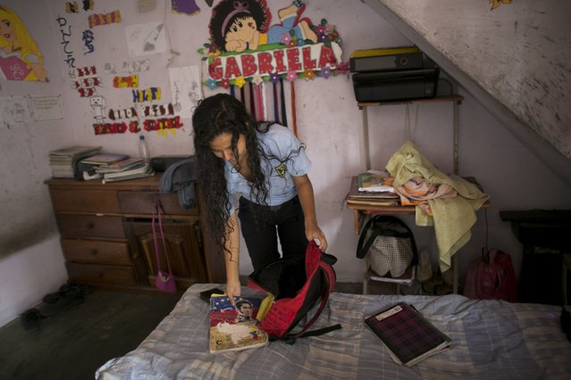 "In this June 1, 2016, Maria Arias packs her backpack in her bedroom, decorated with her middle name ""Gabriela"", in Caracas, Venezuela. Chatty and so studious her classmates call her ""Wikipedia"", Arias started the year at a school with dreams of becoming an accountant and moving to Paris. Her parents saved up to buy her new notebooks, one for each subject, but nine months later, they remain mostly empty due to her teachers not showing up for class, or entire school days being cancelled. (Photo by Ariana Cubillos/AP Photo)"