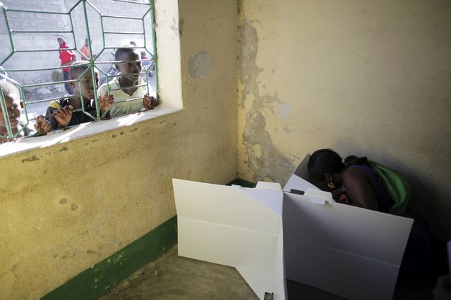 A woman casts her vote as children peek through a window at a polling station in Port-au-Prince, Haiti, August 9, 2015. (Photo by Andres Martinez Casares/Reuters)