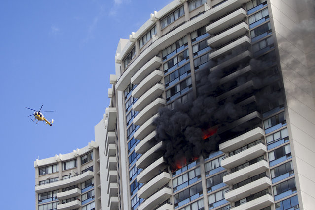 A Honolulu Fire Department helicopter flies near a fire burning on a floor at the Marco Polo apartment complex, Friday, July 14, 2017, in Honolulu. (Photo by Marco Garcia/AP Photo)
