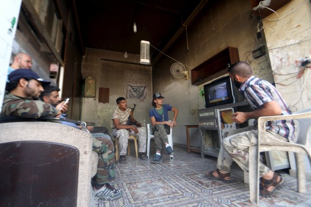"""""""Free Syrian Army"""" fighters watch television while resting in Aleppo, Syria August 10, 2015. (Photo by Abdalrhman Ismail/Reuters)"""
