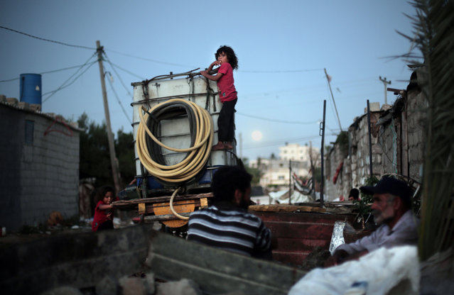 In this Monday, June 20, 2016 photo, Palestinian children climb on a portable tank used to distribute water in el-Zohor slum, on the outskirts of Khan Younis refugee camp, southern Gaza Strip. (Photo by Khalil Hamra/AP Photo)