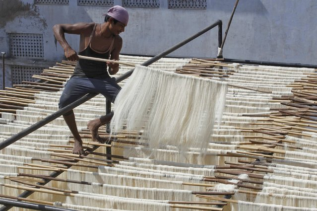 A man hangs strands of vermicelli, a specialty eaten during the Muslim holy fasting month of Ramadan, to dry at a factory in Allahabad, India, June 29, 2016. (Photo by Jitendra Prakash/Reuters)