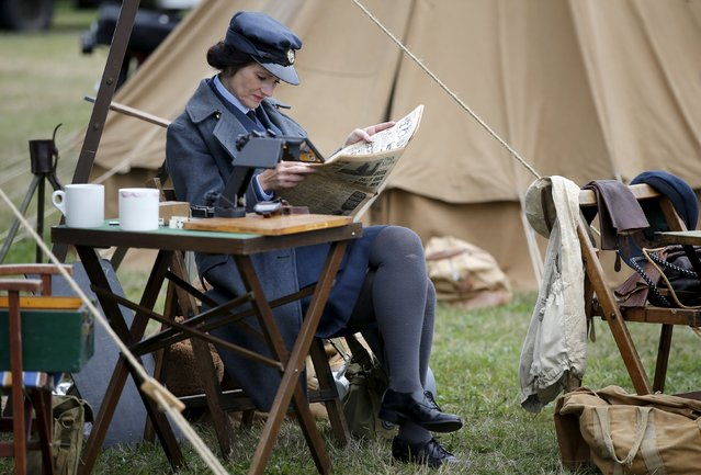 "A ""Battle of Britain"" re-enactor reads a newspaper during a ""Battle of Britain"" commemoration event at Biggin Hill in southern England Britain, August 18, 2015. (Photo by Peter Nicholls/Reuters)"