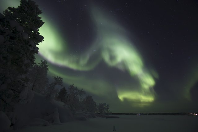A picture taken on December 25, 2017 shows northern lights (aurora borealis), illuminating the sky of Finnish Lapland in Inari. (Photo by Irene Stachon/AFP Photo/Lehtikuva)