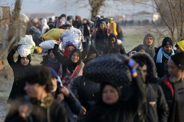 Migrants walk to reach Pazarakule border gate, Edirne, Turkey, at the Turkish-Greek border on Sunday, March 1, 2020. Turkey's President Recep Tayyip Erdogan said his country's borders with Europe were open Saturday, making good on a longstanding threat to let refugees into the continent as thousands of migrants gathered at the frontier with Greece. (Photo by Emre Tazegul/AP Photo)