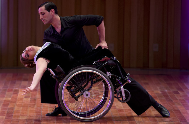 Argentine dancer Pablo Rafael Pereyra dips his partner Gabriela Fernanda Torres, as part of their dance routine in the stage category at the World Tango Championship in Buenos Aires, Argentina, Friday, August 21, 2015. Torres strikes a truly unique pose among the hundreds of dancers at the World Cup of Tango. The 37-year-old says she was paralyzed in a car accident when she was 2 years old, but nonetheless grew up with a love of dancing. (Photo by Natacha Pisarenko/AP Photo)