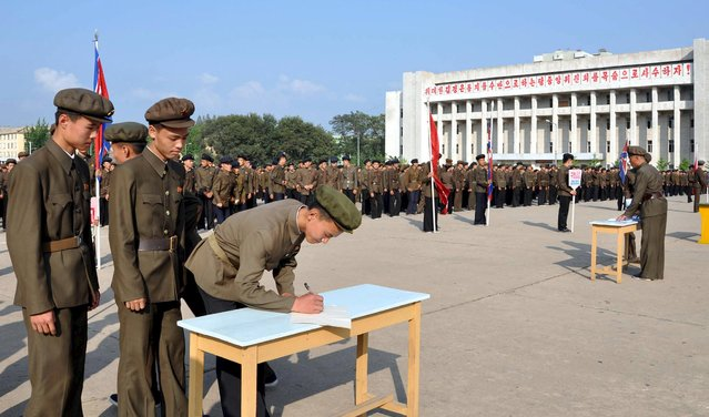 North Koreans sign up to join the army in the midst of political tension with South Korea, in this undated photo released by North Korea's Korean Central News Agency (KCNA) in Pyongyang August 23, 2015. Top aides to the leaders of North and South Korea resumed talks on Sunday after negotiating through the night in a bid to ease tensions involving an exchange of artillery fire that brought the peninsula to the brink of armed conflict. (Photo by Reuters/KCNA)
