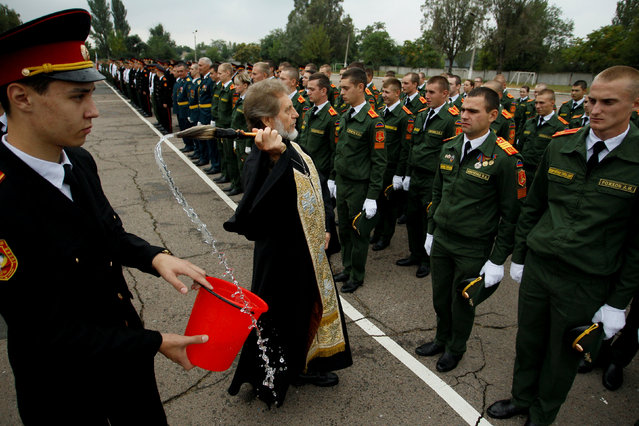 A clergyman sprinkles holy water on cadets of a high military school during a ceremony to mark the beginning of a new academic year in Donetsk, Ukraine September 1, 2017. (Photo by Alexander Ermochenko/Reuters)