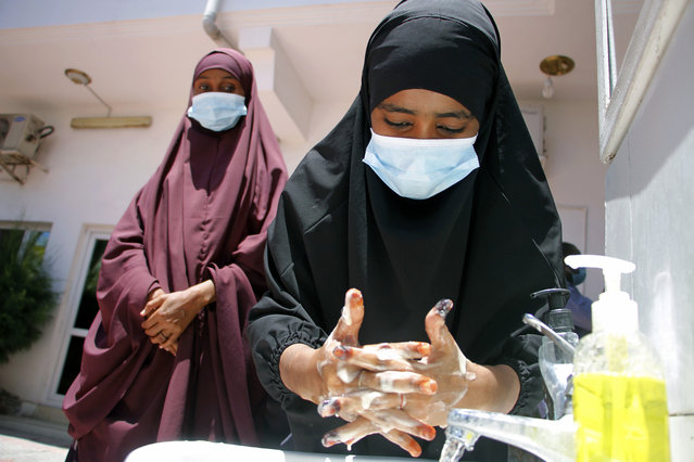 Somali female wash their hands during coronavirus awareness training conducted by the local paramedics and doctors in Somali capital Mogadishu, Thursday, March, 19, 2020. Somalia's government has announced the closure of schools universities and a ban or large gathering and events for two weeks effective. For most people, the new coronavirus causes only mild or moderate symptoms such as fever and cough and the vast majority recover in 2-6 weeks but for some especially older adults and the people with existing health issues, the virus that causes COVID-19 can result in more severe illness, including pneumonia. (Photo by Farah Abdi Warsameh/AP Photo)