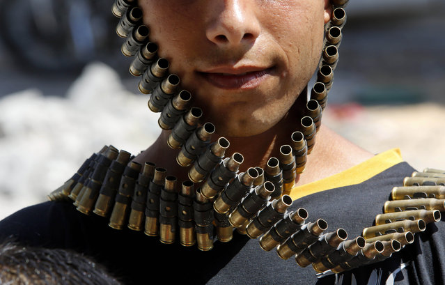 A Palestinian youth wraps a bandolier of spent bullets leftover by the Israeli army, next to his destroyed home in Beit Hanoun, Gaza Strip, Monday, August 11, 2014. (Photo by Hatem Moussa/AP Photo)