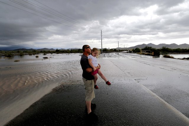 Josh Groves, and his daughter Abagayle Groves, 3, wait to cross the road as flash flood waters overrun Skunk Creek through the Sonoran Desert, Tuesday, August 19, 2014, in northwestern Phoenix. Flooding from heavy rain in the Phoenix area has forced authorities to close several major roads, including a portion of Interstate 17 about 25 miles north of the city. (Photo by Matt York/AP Photo)