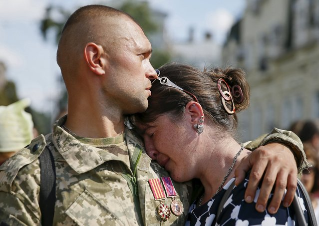 A man embraces his girlfriend in Kiev as they commemorate Ukrainian servicemen killed a year ago during fights with pro-Russian rebels near the town of Ilovaysk in eastern Ukraine, August 29, 2015. (Photo by Valentyn Ogirenko/Reuters)