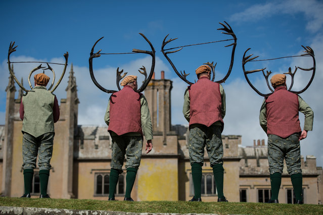 """Dancers turn to face the audience after performing the """"Abbots Bromley Horn Dance"""" in the grounds of Blithfield Hall, near the village of Abbots Bromley, central England, on September 11, 2017. The Abbots Bromley Horn Dance is an English folk dance whose origins date back to the middle ages and is performed annually on Wakes Monday. The dancers comprise of six Deer-men bearing reindeer antlers, a Fool, a Hobby Horse, a Bowman and Maid Marian. Musical accompaniment to the dance is provided by two accordion players and a boy playing a triangle. (Photo by Oli Scarff/AFP Photo)"""