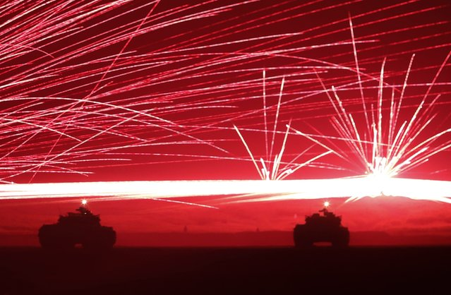 Tracer bullets ricochet off their targets as Japanese Ground Self-Defence Force tanks fire their machine guns during a night session of an annual training exercise at Higashifuji training field near Mount Fuji in Gotemba, west of Tokyo, August 19, 2014. Japanese battle tanks, helicopters and elite troops stormed the foothills of Mount Fuji Tuesday in a first-of-its-kind display of the tactics and equipment the nation's military could use to defend or retake islands in and around the East China Sea. (Photo by Yuya Shino/Reuters)
