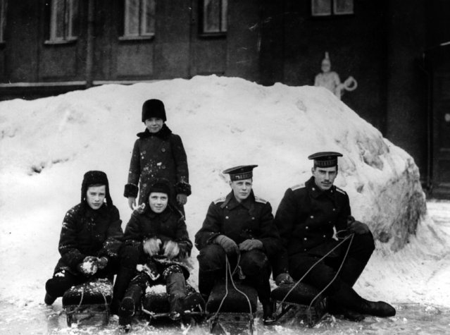Royal children play in the snow outside the Anichkov Palace, Petrograd, residence of their grandmother, Empress Marie Feodorovna, circa 1913. They are nephews of Tsar Nicholas II, and sons of Grand Duke Alexander Mikhailovich and Grand Duchess Xenia Alexandrovna of Russia.  From left to right in front are:  Prince Rostislav Alexandrovitch, Prince Dmitri Alexandrovitch, Prince Nikita Alexandrovitch, and Prince Andrei Alexandrovitch and behind them stands Prince Vasili Alexandrovitch.