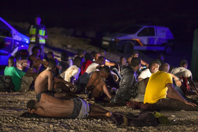 African migrants rest after arriving on a fishing boat at Las Carpinteras beach in the Canary Island of Gran Canaria, Spain, September 1, 2015. Around 60 people, including six women and a two-year-old child, were aboard the fishing boat, according to local authorities. Picture taken September 1, 2015. (Photo by Borja Suarez/Reuters)