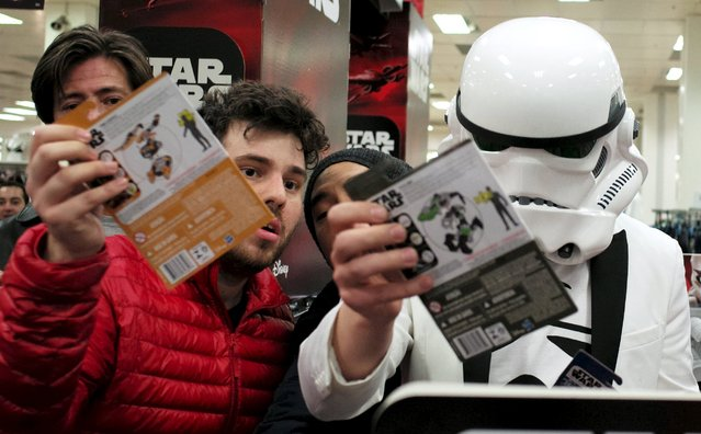 """A shopper wearing an Imperial Stormtrooper helmet collects new toys from the upcoming film """"Star Wars: The Force Awakens"""" just after midnight on """"Force Friday"""" in Sydney, September 4, 2015. (Photo by Jason Reed/Reuters)"""