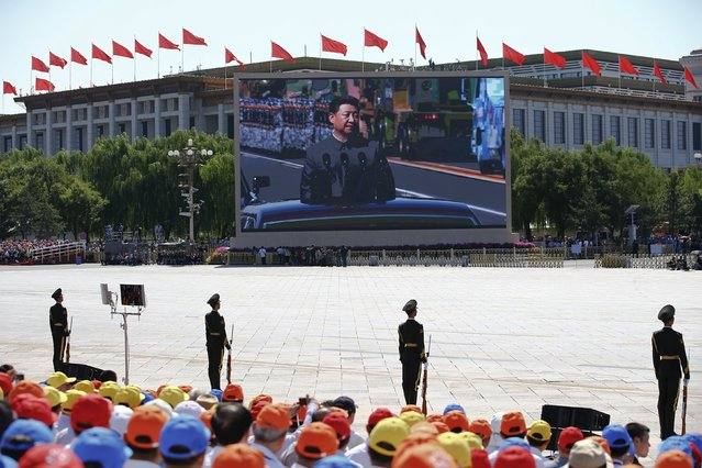 Chinese President Xi Jinping is shown on a big screen at Tiananmen Square as he reviews troops at the beginning of the military parade marking the 70th anniversary of the end of World War Two, in Beijing, China, September 3, 2015. (Photo by Damir Sagolj/Reuters)