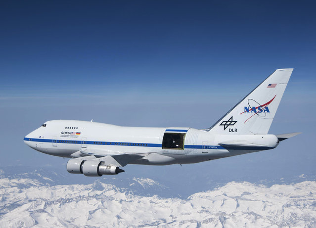 """This undated photo provided by NASA shows SOFIA over the snow-covered Sierra Nevada mountains with its telescope door open during a test flight. The world's largest airborne observatory was supposed to be parked in Seattle this week, so thousands of scientists attending the """"Super Bowl of Astronomy"""" could behold this marvel: a Boeing 747, like this one shown, for example, outfitted with a massive telescope used to study the fundamental mysteries of the universe. (Photo by Jim Ross/NASA via AP Photo)"""