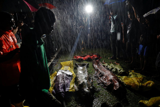 People gather under heavy rain around bodies of Rohingya refugees after their boat with passengers fleeing from Myanmar capsized off the Inani beach near Cox's Bazar, Bangladesh September 28, 2017. (Photo by Damir Sagolj/Reuters)