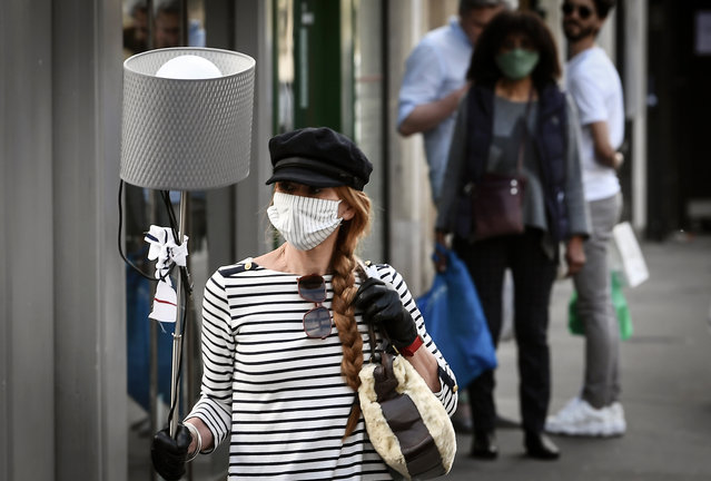 A woman wearing a face mask walks with a lamp in a street of Paris on April 25, 2020 the 40th day of a strict lockdown aimed at curbing the spread of the COVID-19 pandemic, caused by the novel coronavirus. (Photo by Alain Jocard/AFP Photo)