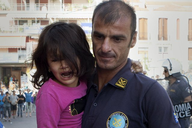 A Greek coast guard officer carries an Afghan refugee girl away from scuffles between Greek police and Afghan refugees that protested over priority for a registration procedure at the port of Mytilene on the Greek island of Lesbos, September 6, 2015. (Photo by Dimitris Michalakis/Reuters)