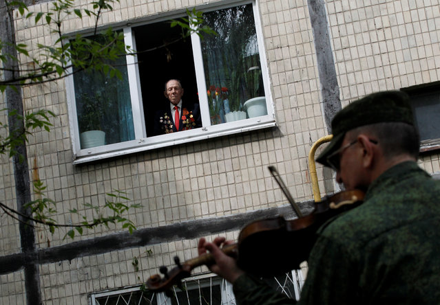 A musician dressed in a military uniform plays the violin while congratulating veteran Mikhail Morozov, 96, during the celebrations of Victory Day, which marks the anniversary of the victory over Nazi Germany in World War Two, amid the outbreak of the coronavirus disease (COVID-19) in Donetsk, Ukraine on May 9, 2020. (Photo by Alexander Ermochenko/Reuters)