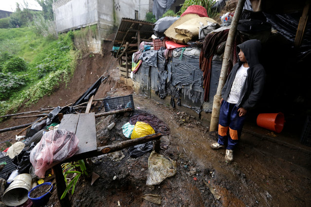 A child shields from the rain as he stands near his house damaged after a mudslide following heavy showers caused by the passing of Tropical Storm Earl, in the town of Huauchinango, in Puebla state, Mexico, August 7, 2016. (Photo by Reuters/Stringer)