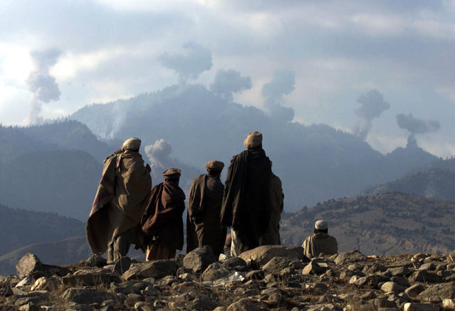 Anti-Taliban Afghan fighters watch several explosions from U.S. bombings in the Tora Bora mountains in Afghanistan December 16, 2001. (Photo by Erik de Castro/Reuters)
