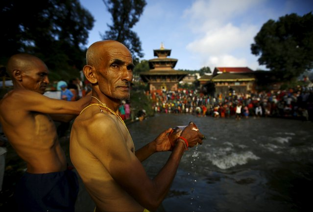Hindu devotees perform a ritual near the bank of Bagmati River during Kuse Aunse (Father's Day) at Gokarna Temple in Kathmandu, Nepal September 13, 2015. Hindus all over the country, whose fathers have passed away, come to the temple for worship, holy dips, and to present offerings on this occasion. (Photo by Navesh Chitrakar/Reuters)