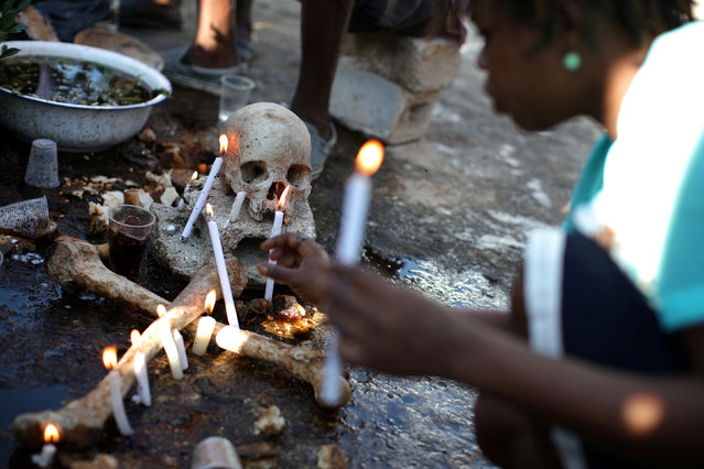 A voodoo believer makes offerings during celebrations at the cemetery of Port-au-Prince, Haiti, November 1, 2017. (Photo by Andres Martinez Casares/Reuters)