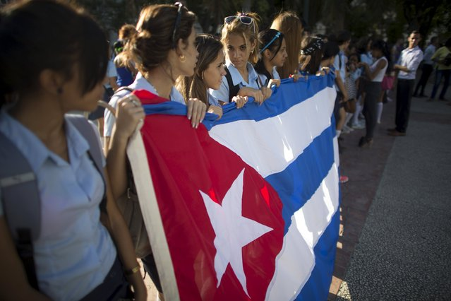 Pre-university students hold a Cuban flag as they walk in downtown Havana to mark the first day of class for the 2015-2016 course, September 1, 2015. (Photo by Alexandre Meneghini/Reuters)