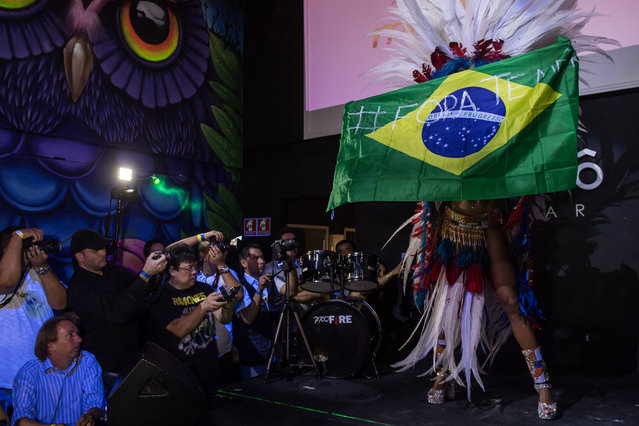 "Rosie Oliveira from Amazonas holds a Brazilian national flag with an inscription reading ""Temer out"" (a reference to Brazilian President Michel Temer) during the Miss Bumbum Brazil 2017 pageant in Sao Paulo on November 07, 2017. (Photo by Nelson Almeida/AFP Photo)"