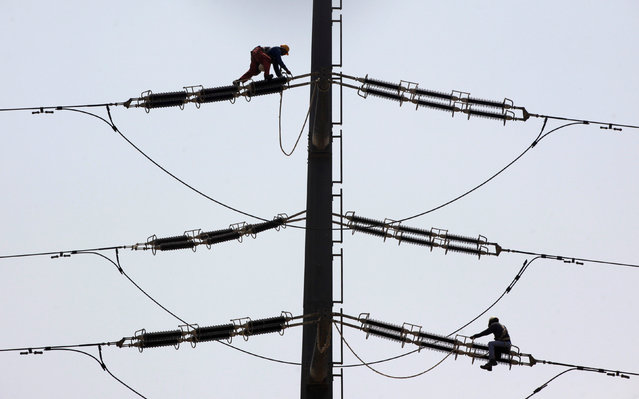 Employees of K-Electric fix cables on a power transmission tower in Karachi, Pakistan, August 22, 2016. (Photo by Akhtar Soomro/Reuters)