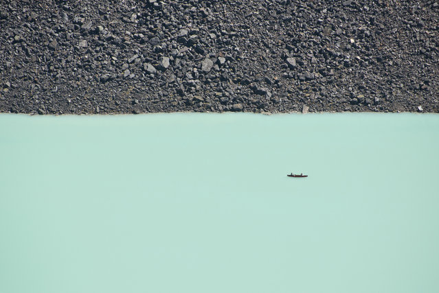 """""""A Canoe ride on Lake Louise"""". This disorienting photo was taken from a cliff overlooking Lake Louise in Banff national park. The two people are enjoying a canoe ride on Lake Louise's turquoise waters. Even boulders the size of large cars seem like pebbles from a high vantage point. Photo location: Lake Louise, Banff National Park, Alberta, Canada. (Photo and caption by Ben Leshchinsky/National Geographic Photo Contest)"""