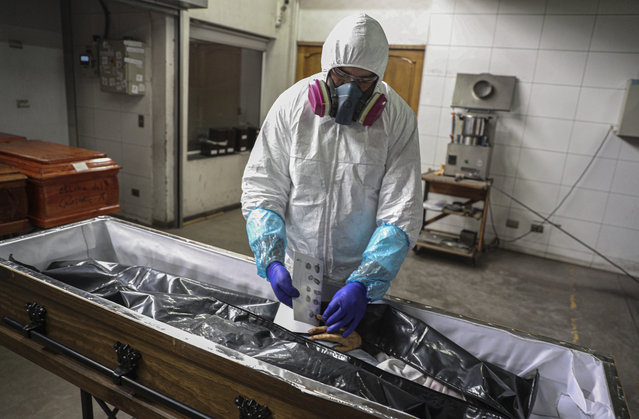 An employee takes the fingerprints of a woman who died from the new coronavirus before her remains are cremated at La Recoleta crematorium in Santiago, Chile, Saturday, June 27, 2020. The Ministry of Health reported on Saturday the highest number of deaths in Chile since the start of the pandemic. (Photo by Esteban Felix/AP Photo)