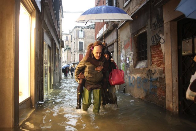 People walk in a flooded street during a period of seasonal high water in Venice November 11, 2012. The water level in the canal city rose to 149 cm (59 inches) above normal, according to local monitoring institute Center Weather Warnings and Tides. (Photo by Manuel Silvestri/Reuters)