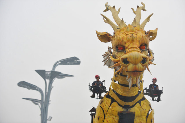 """Actors rehearse with the French mechanical installation """"LongMa"""", which means a fine horse in the shape of a dragon, during a press conference at the center of the Olympic Green in Beijing on October 10, 2014. (Photo by Mandy Wang/AFP Photo)"""