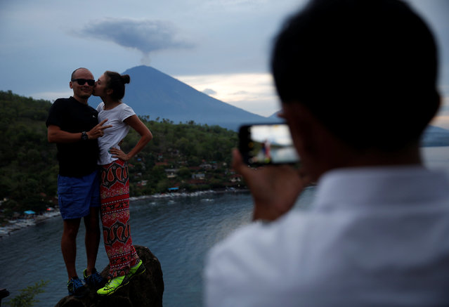 Tourists from Russia pose while having their photograph taken with Mount Agung volcano erupting in the background from Amed, Karangasem Regency, Bali, Indonesia, November 30, 2017. (Photo by Darren Whiteside/Reuters)