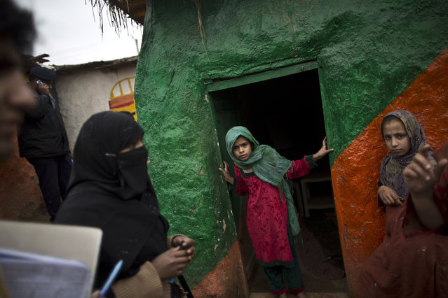 In this Monday, March 10, 2014, photo, a Pakistani health worker, left, checks with a teacher whether schoolchildren need a polio vaccine at a makeshift school on the outskirts of Islamabad, Pakistan. (Photo by Muhammed Muheisen/AP Photo)